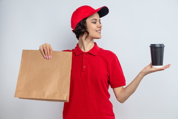 Pleased young pretty delivery woman holding paper food packaging and looking at takeaway cup