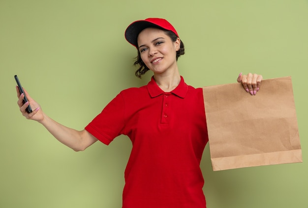 Pleased young pretty delivery woman holding paper food packaging and phone