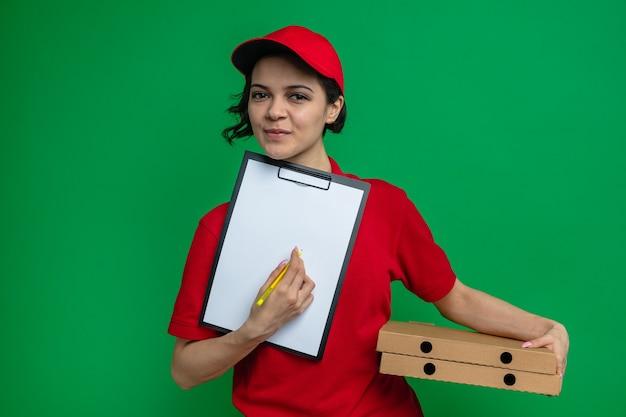 Lieta giovane graziosa donna delle consegne che tiene in mano scatole per pizza e appunti