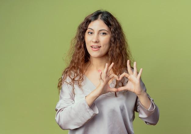 Soddisfatto giovane impiegato grazioso femminile che mostra gesto del cuore isolato sulla parete verde oliva