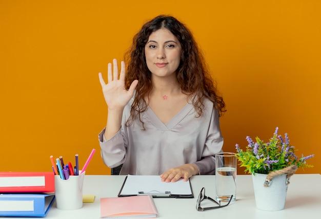 오렌지에 고립 된 안녕하세요 제스처를 보여주는 사무실 도구로 책상에 앉아 기쁘게 젊은 예쁜 여성 회사원