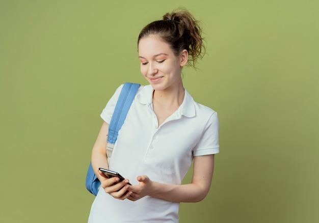 コピースペースで緑の背景に分離された携帯電話を保持し、見てバックバッグを身に着けている若いきれいな女性の学生を喜ばせる