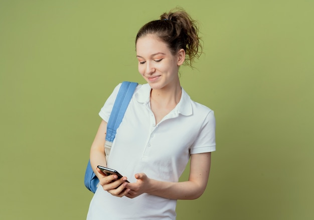 Soddisfatto giovane studentessa graziosa che indossa la borsa posteriore che tiene e guardando il telefono cellulare isolato su sfondo verde con spazio di copia