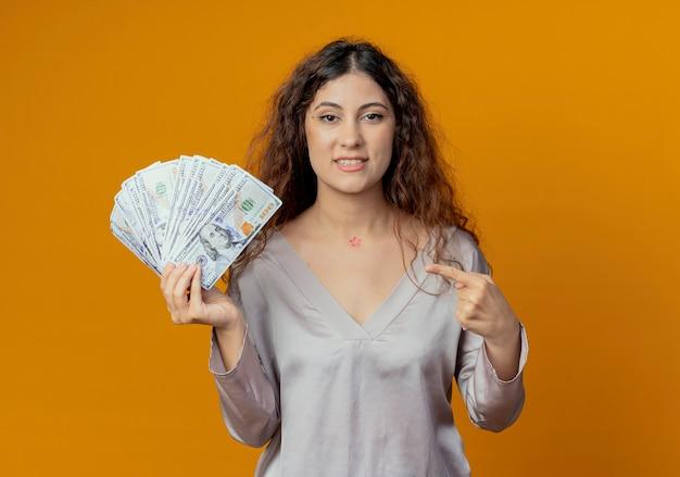 들고 기쁘게 젊은 예쁜 여자와 노란색 벽에 고립 된 현금 포인트
