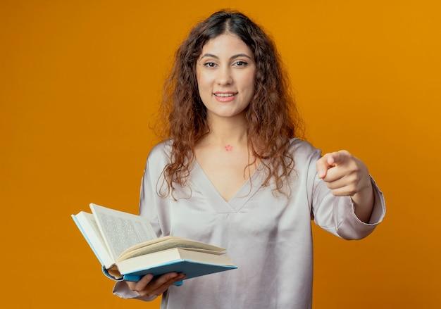 책을 들고 노란색 벽에 고립 된 제스처를 보여주는 기쁘게 젊은 예쁜 여자