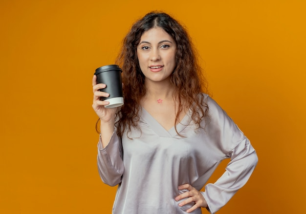 一杯のコーヒーを保持し、黄色の壁に分離された腰に手を置いて喜んで若いかわいい女の子