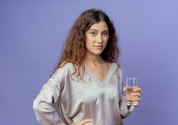 水のガラスを保持し、青い壁に分離された腰に手を置いて喜んで若いかわいい女の子