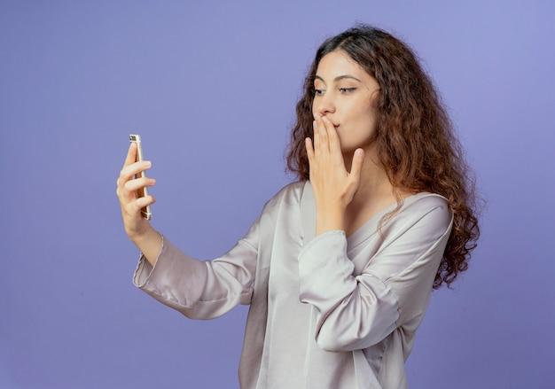 Soddisfatto giovane ragazza graziosa che tiene e che guarda il telefono e la bocca coperta con la mano isolata sulla parete blu