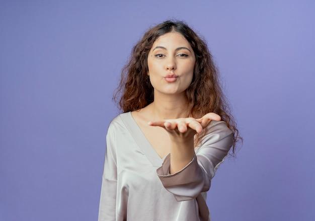 Lieta giovane ragazza graziosa tendendo la mano alla fotocamera e mostrando il gesto di bacio isolato sull'azzurro
