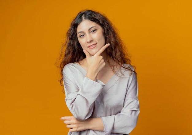 黄色の壁に隔離されたあごの下に手を置いて喜んで若いかわいい女の子 無料写真