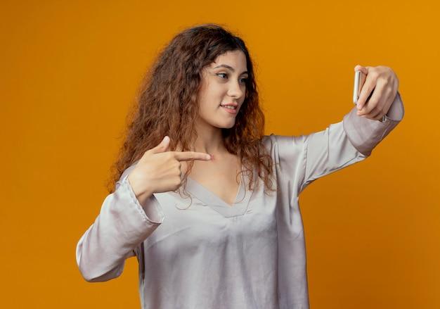 기쁘게 젊은 예쁜 여자 노란색 벽에 고립 된 전화에서 셀카와 포인트를