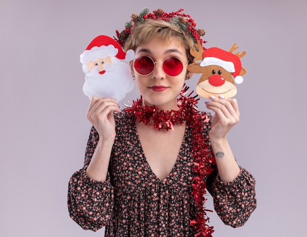 Pleased young pretty girl wearing christmas head wreath and tinsel garland around neck with glasses holding christmas reindeer and santa claus paper ornaments near head looking at side isolated on white wall