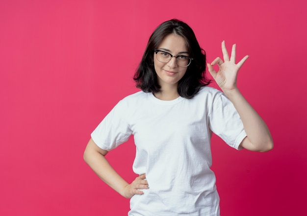 Lieta giovane ragazza carina con gli occhiali mettendo la mano sulla vita e facendo segno ok