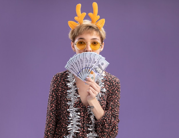 Pleased young pretty girl wearing reindeer antlers headband and tinsel garland around neck with glasses holding money looking at camera from behind it isolated on purple background with copy space
