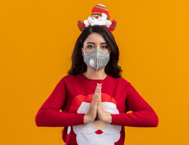 행복 한 젊은 예쁜 여자 산타 클로스 머리 띠와 스웨터를 입고 보호 마스크와 함께 오렌지 배경에 고립 된 손을 함께 유지하는 카메라를보고