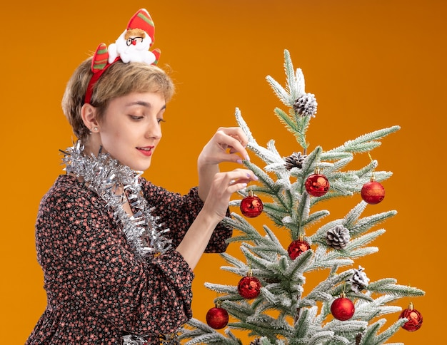 Pleased young pretty girl wearing santa claus headband and tinsel garland around neck standing in profile view near christmas tree looking at it decorating it with christmas baubles isolated on orange wall