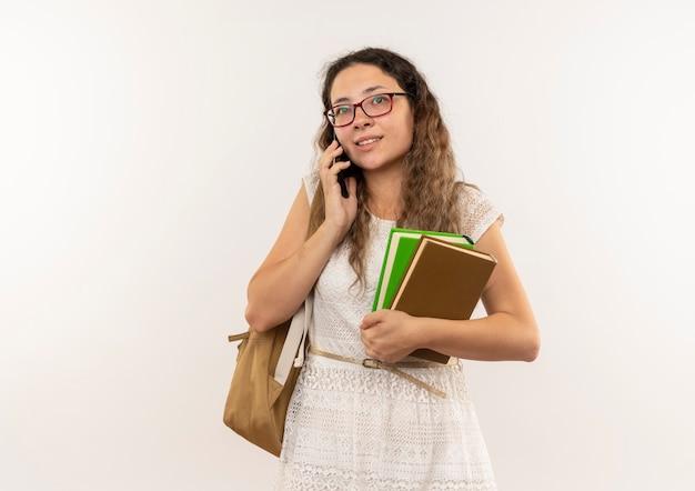 흰색 벽에 고립 된 전화 통화 책을 들고 안경과 다시 가방을 입고 기쁘게 젊은 예쁜 여학생