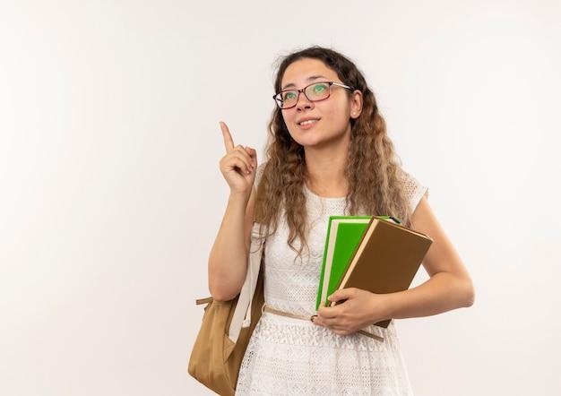 Soddisfatto giovane studentessa graziosa con gli occhiali e borsa posteriore in possesso di libri alzando il dito isolato sul muro bianco