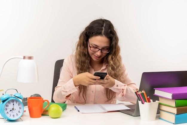 Lieta giovane studentessa graziosa con gli occhiali seduto alla scrivania con gli strumenti della scuola facendo i compiti utilizzando il suo telefono isolato sul muro bianco