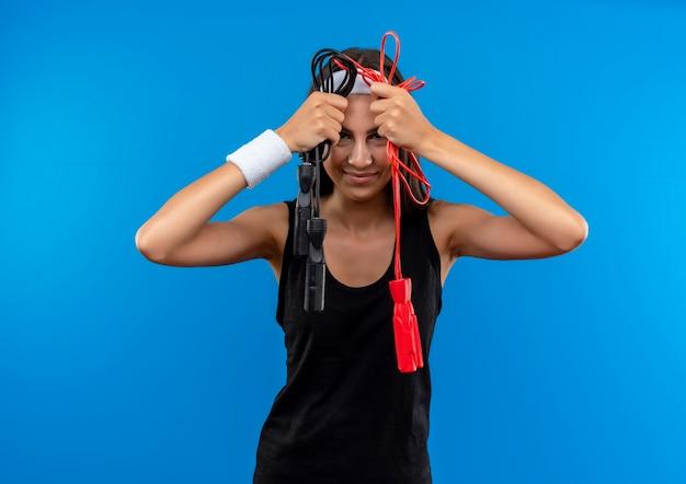 Довольная молодая симпатичная спортивная девушка с ободком и браслетом держит скакалки возле головы, изолированной на синем пространстве