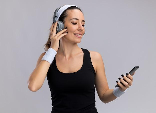 Довольная молодая симпатичная спортивная девушка с головной повязкой и браслетами с наушниками держит и смотрит на мобильный телефон, касаясь наушников, изолированных на белой стене