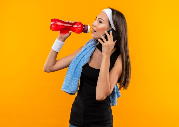 Lieta giovane ragazza abbastanza sportiva che indossa la fascia e il braccialetto cercando di bere acqua dalla bottiglia e parlando al telefono guardando il lato isolato sullo spazio arancione
