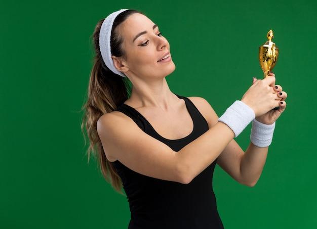 Felice giovane ragazza piuttosto sportiva che indossa fascia e braccialetti che tengono e guardano la coppa del vincitore isolata sulla parete verde con spazio per le copie