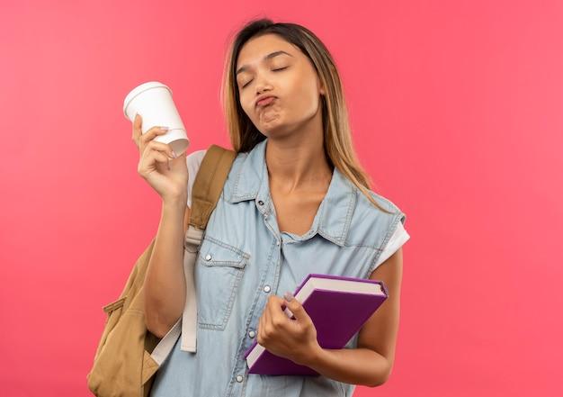 Lieta giovane bella studentessa che indossa la borsa posteriore che tiene il libro e la tazza di caffè in plastica con gli occhi chiusi isolati sulla parete rosa