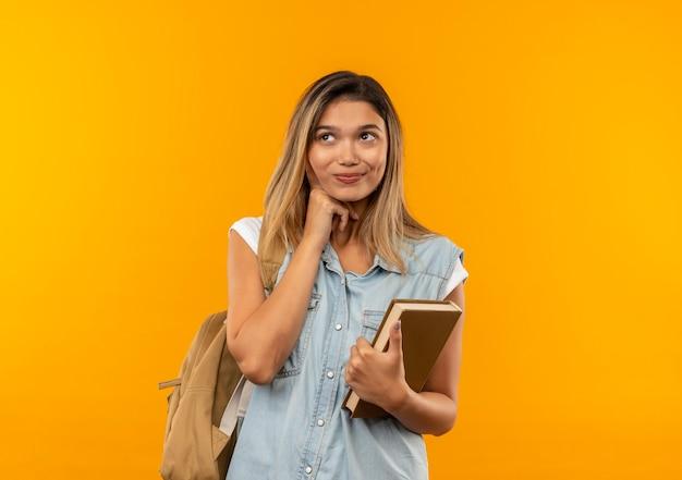 Soddisfatto giovane ragazza graziosa dell'allievo che indossa la borsa posteriore che tiene il libro mettendo la mano sotto il mento e guardando il lato isolato sulla parete arancione