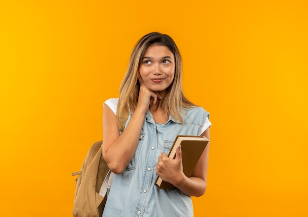 あごの下に手を置き、オレンジ色の壁に隔離された側を見て本を保持しているバックバッグを身に着けている若いかわいい学生の女の子を喜ばせる