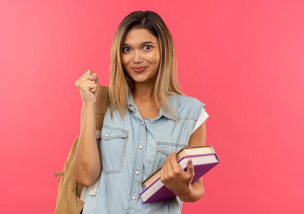 Lieta giovane studentessa graziosa che indossa la borsa posteriore con libri e pugno di serraggio isolato sulla parete rosa