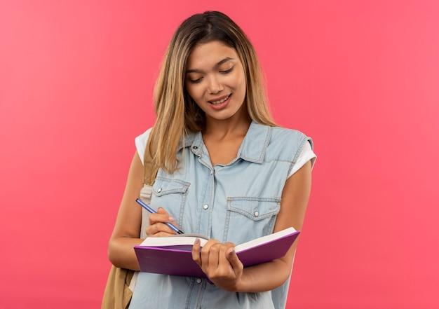 Lieta giovane bella studentessa indossa la borsa posteriore che tiene e guardando il libro aperto con la penna in mano isolato sulla parete rosa