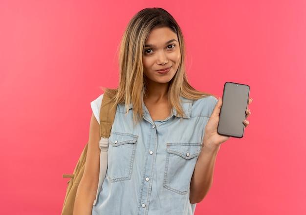 ピンクの壁に隔離された正面に携帯電話を示すバックバッグを身に着けている若いかわいい学生の女の子を喜ばせる