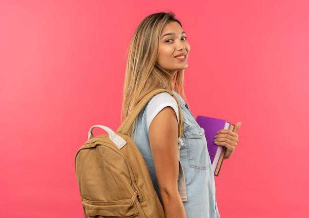 Lieta giovane studentessa graziosa che indossa la borsa posteriore in piedi in vista di profilo tenendo libri isolati sulla parete rosa