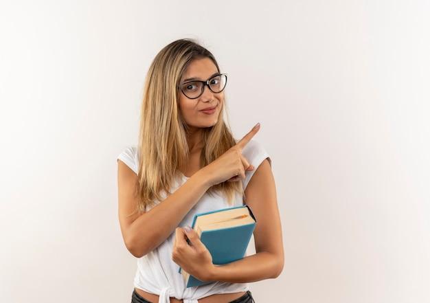 白い壁で隔離の側を指している本を保持している眼鏡とバックバッグを身に着けている若いかわいい学生の女の子を喜ばせる