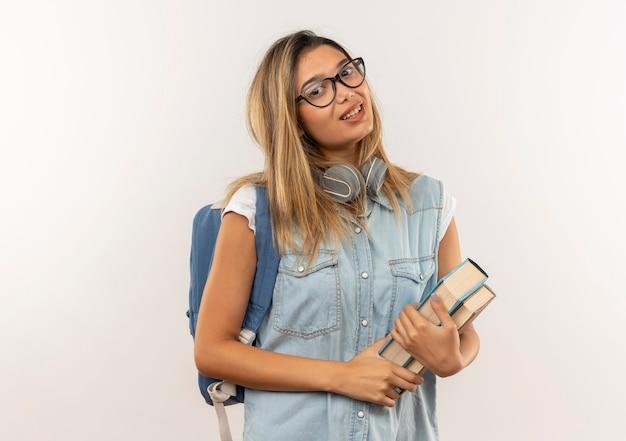 흰 벽에 고립 된 책을 들고 목에 헤드폰으로 안경과 백 가방을 입고 기쁘게 젊은 예쁜 학생 소녀