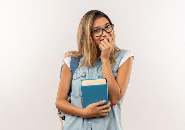 Lieta giovane bella studentessa con gli occhiali e borsa posteriore che tiene il libro mettendo il dito sul labbro isolato sul muro bianco