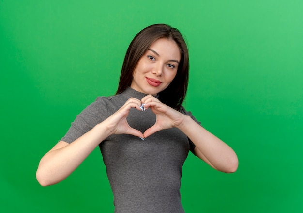Pleased young pretty woman doing heart sign isolated on green background