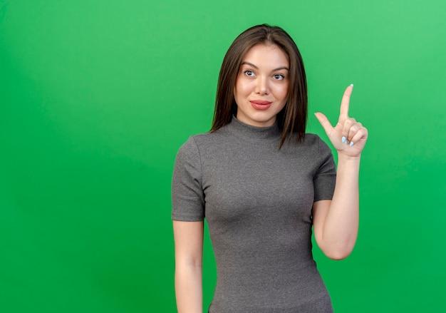 복사본 공간이 녹색 배경에 고립 된 측면을보고 권총 제스처를 하 고 기쁘게 젊은 예쁜 여자