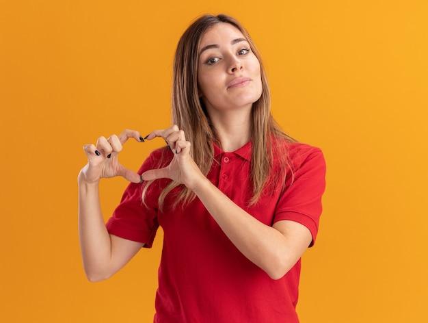 Lieta giovane donna graziosa gesti il segno della mano del cuore isolato sulla parete arancione