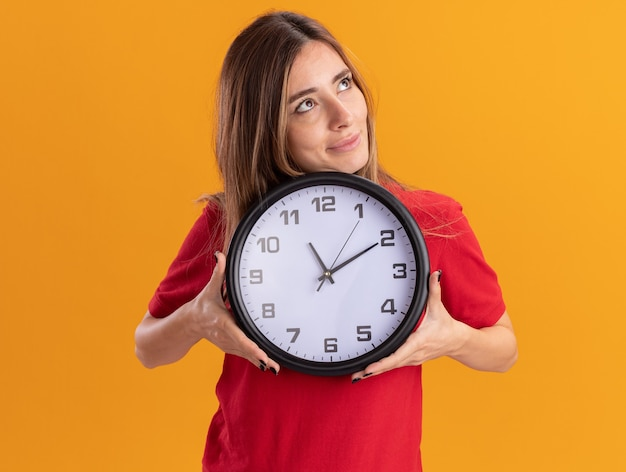 Довольная молодая красивая женщина держит часы и смотрит на сторону, изолированную на оранжевой стене