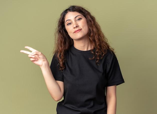 Довольная молодая красивая женщина, смотрящая на фронт, делает знак мира, изолированного на оливково-зеленой стене