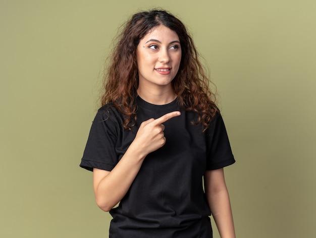 Piacevole giovane donna graziosa che guarda e indica il lato isolato sulla parete verde oliva con spazio di copia