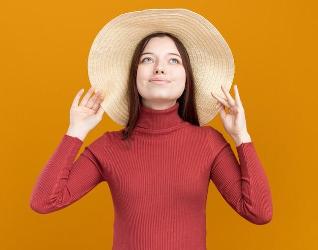 Довольная молодая красивая женщина в пляжной шляпе, хватая шляпу, глядя вверх изолирована на оранжевой стене