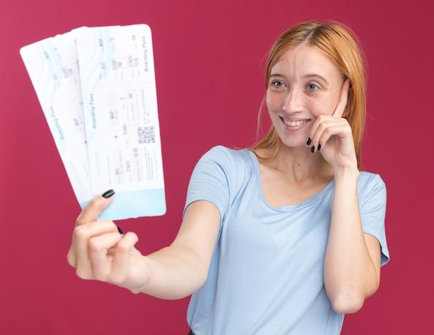 La giovane ragazza rossa dello zenzero piacevole con le lentiggini mette il dito sulla tempia e tiene i biglietti aerei isolati sulla parete rosa con lo spazio della copia