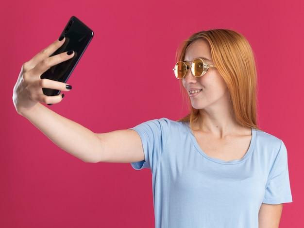 Lieta giovane ragazza rossa dello zenzero con le lentiggini in occhiali da sole tenendo e guardando il telefono prendendo selfie sul rosa