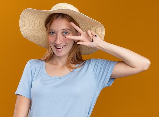 Довольная рыжая рыжая девушка с веснушками в пляжной шляпе показывает знак победы на оранжевом