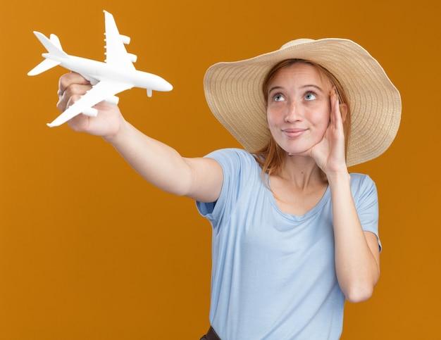 Felice giovane ragazza rossa zenzero con lentiggini che indossa cappello da spiaggia mette la mano sul viso e tiene il modello di aereo guardando in alto