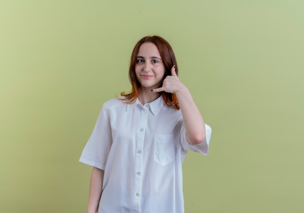 コピースペースでオリーブグリーンに分離された電話ジェスチャーを示す喜んで若い赤毛の女の子