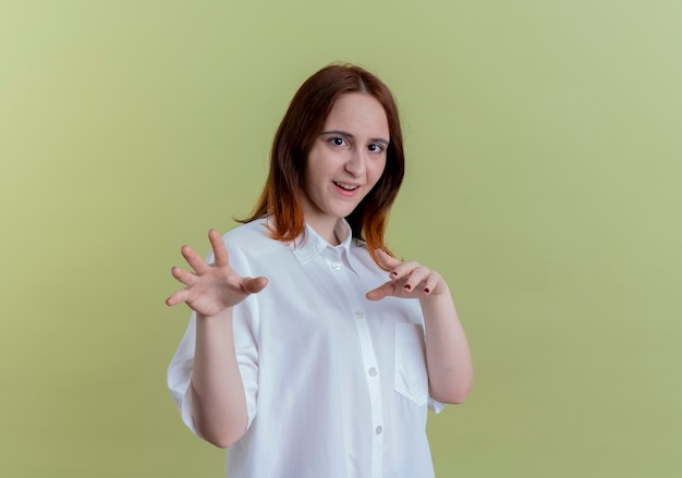 Felice giovane ragazza rossa che mostra stile tigre isolato su verde oliva
